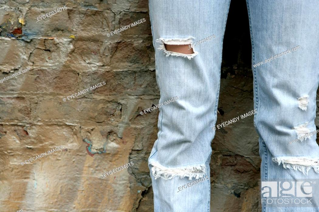 Stock Photo: View of torn jeans worn by a woman.