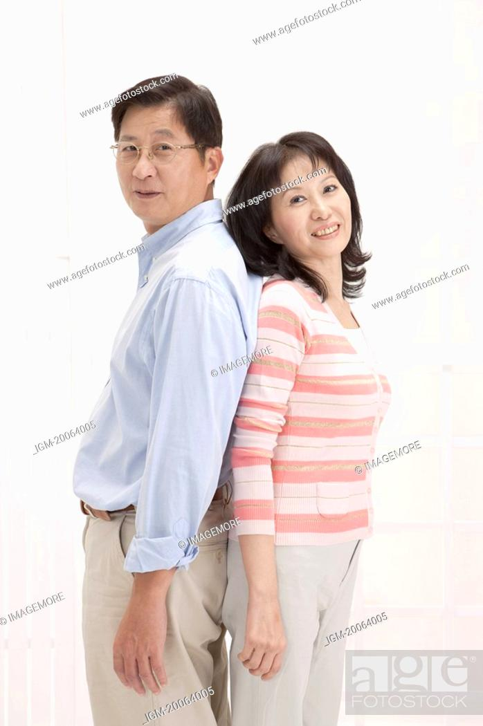 Stock Photo: Couple, Couple standing of back to back and looking at the camera with smile.