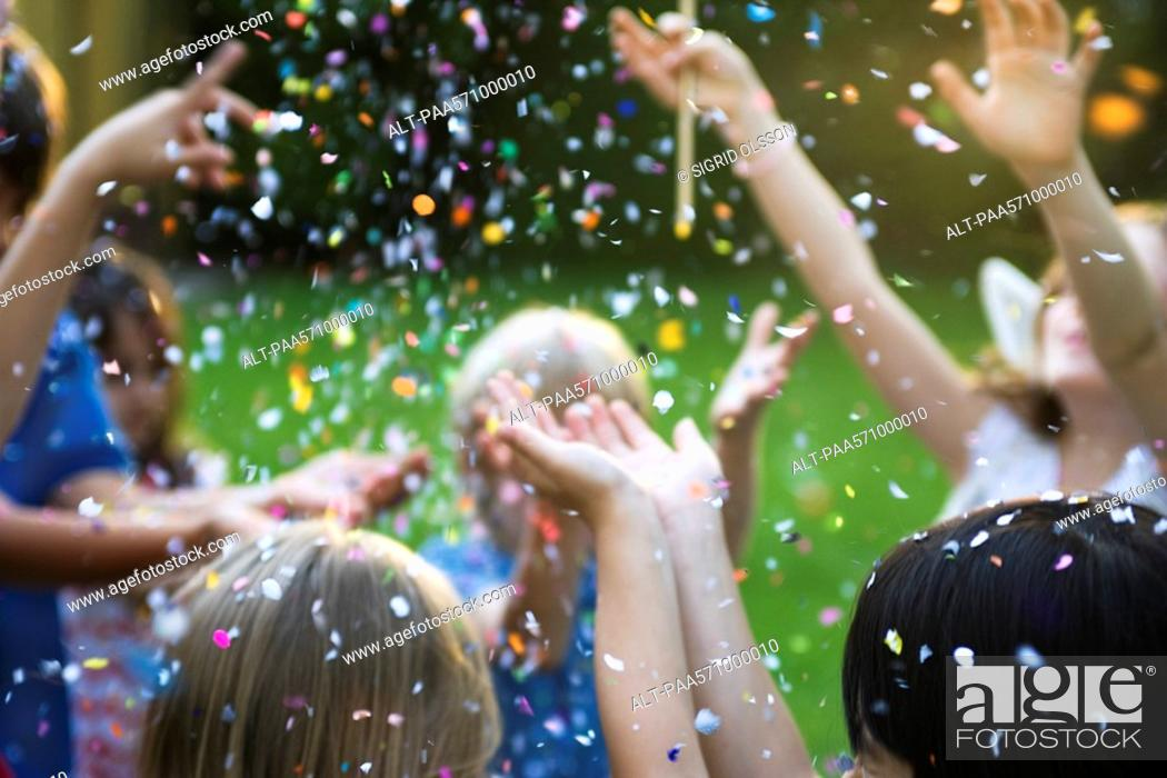 Stock Photo: Children showered in falling confetti.