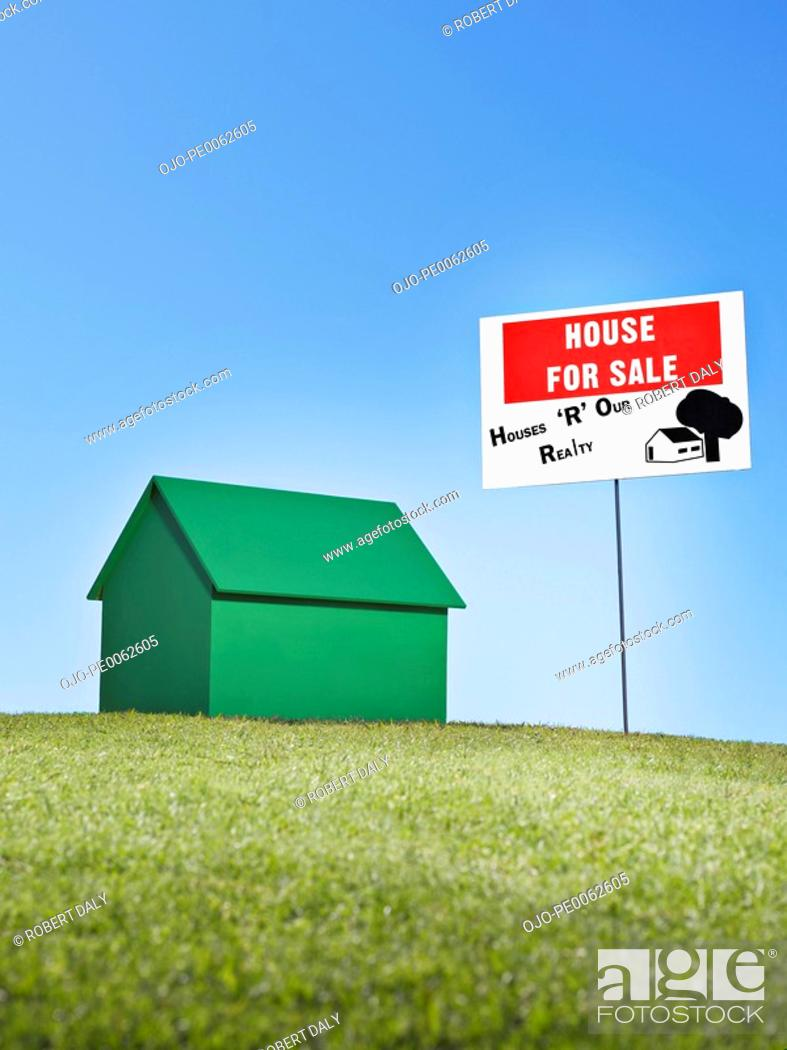 """Stock Photo: Small model house next to """"for sale"""" sign."""