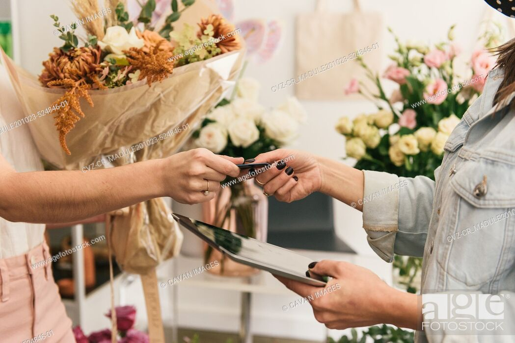 Stock Photo: Close up of customer handing credit card to tablet holding shop owner.