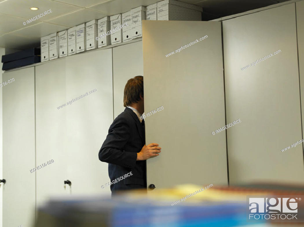 Stock Photo: Office worker looking in cupboard.