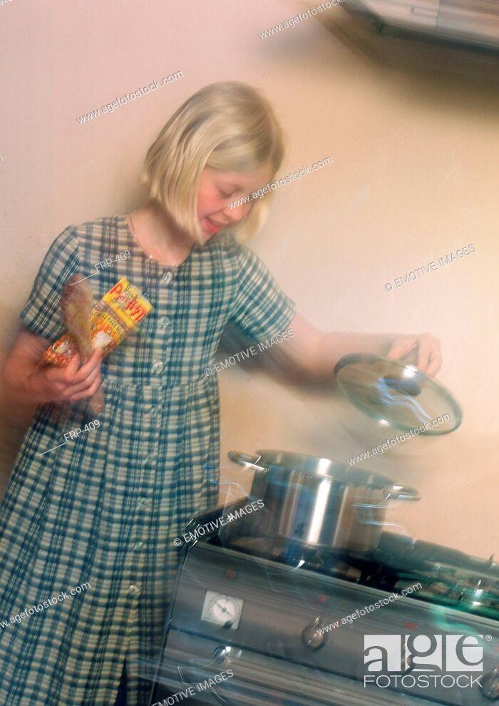 Imagen: Girl cooking in kitchen.