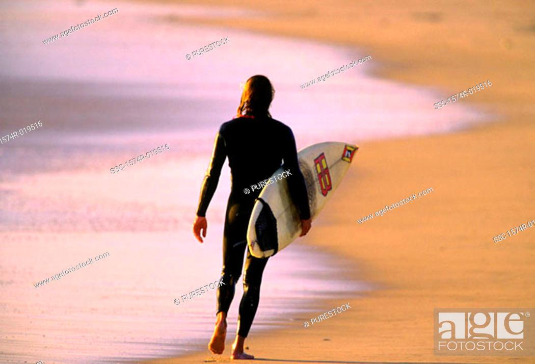 Stock Photo: Surfer walking along the beach.