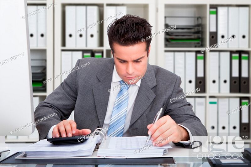 Stock Photo: Portrait Of Happy Young Businessman Sitting At Desk Calculating Finance.