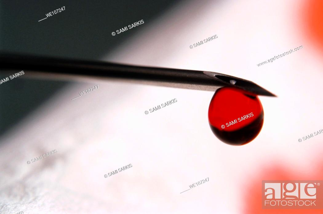 Stock Photo: Drop of blood at the end of a syringe.