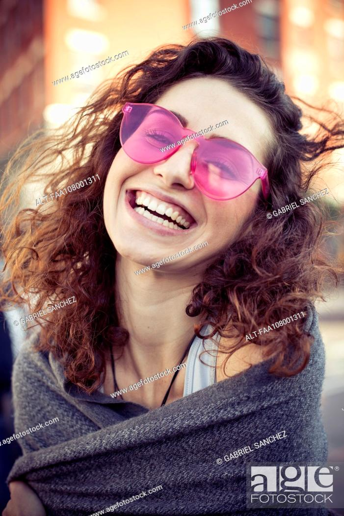 Stock Photo: Woman wearing pink sunglasses, laughing, portrait.
