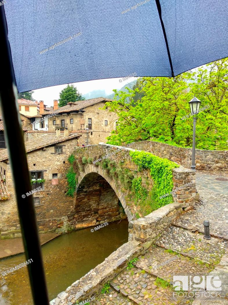 Stock Photo: Old bridge in Potes in a rainy day with an umbrella. Potes, Cantabria, Spain.
