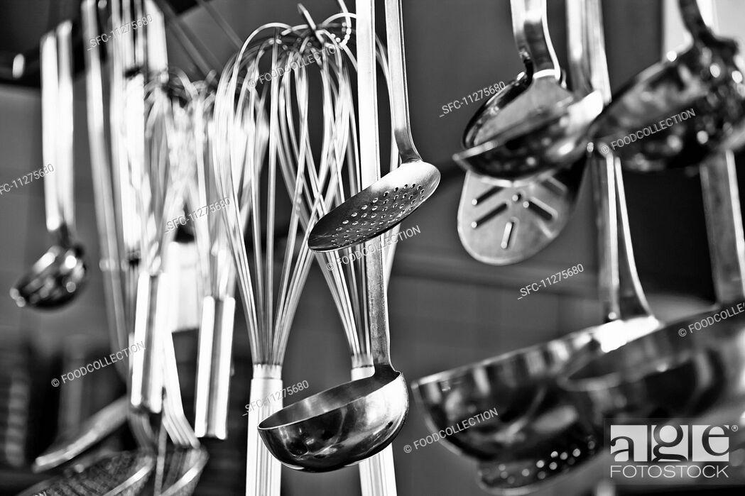 Imagen: Cooking utensils hanging in a restaurant kitchen.