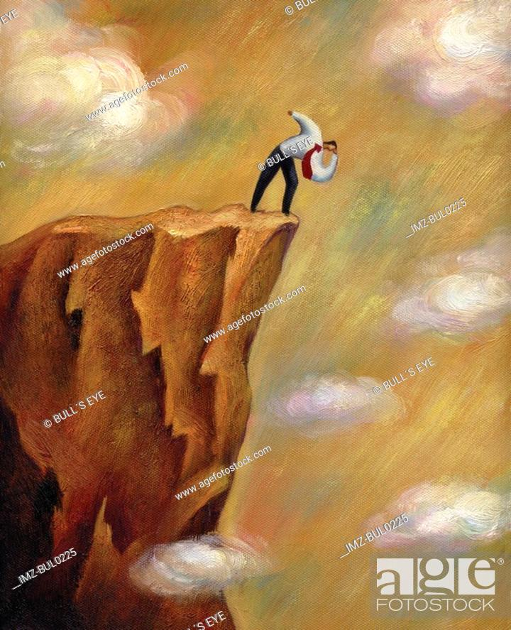 Stock Photo: Businessman looking down over the edge of a cliff.