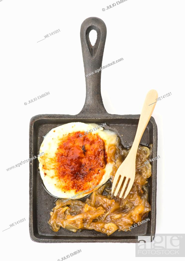 Photo de stock: slice of goat cheese on caramelized onion on iron frying pan.