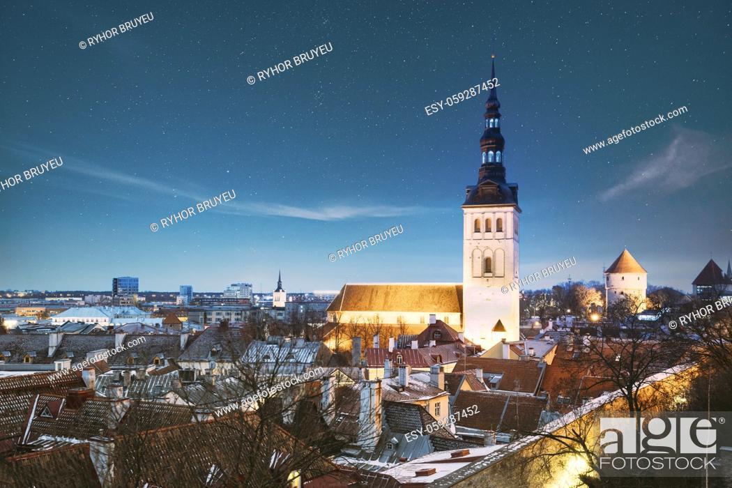 Stock Photo: Tallinn, Estonia. Night Starry Sky Above Traditional Old Architecture Skyline In Old Town. St. Nicholas Church - Niguliste Kirik In Winter Evening Night.