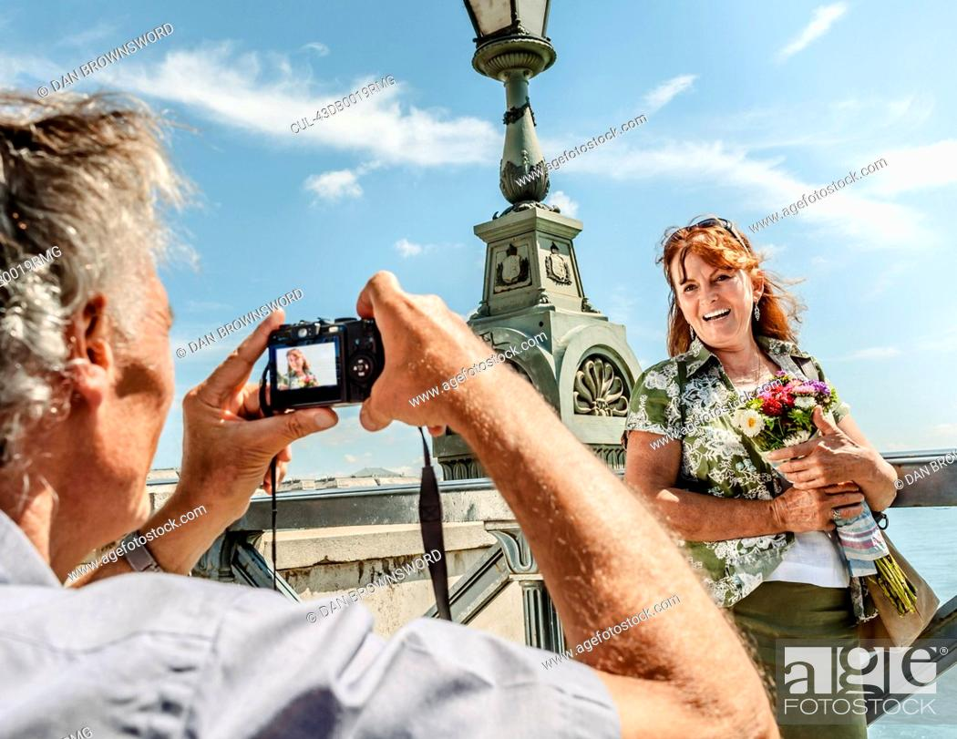 Stock Photo: Older man taking picture of wife.