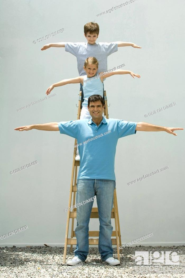 Stock Photo: Boy and girl standing on ladder with arms in the air, father standing on the ground, all smiling at camera.
