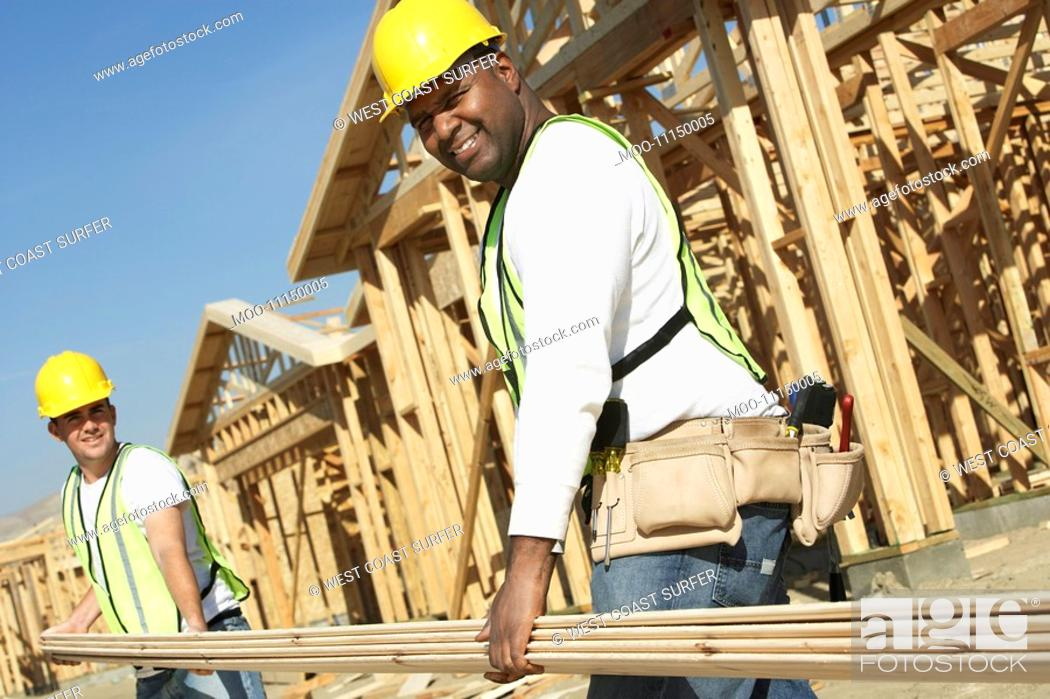 Stock Photo: Construction workers carrying boards at construction Site.