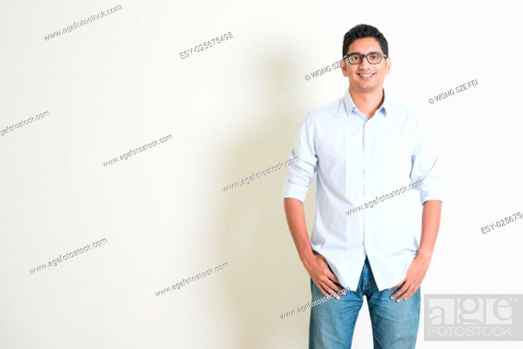 Photo de stock: Portrait of handsome casual business Indian guy smiling, hands in pocket, standing on plain background with shadow, copy space at side.