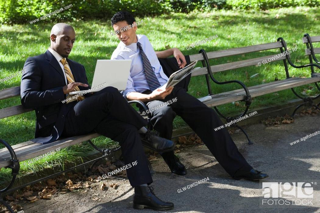 Stock Photo: Two businessmen sitting on a bench in a park and looking at a laptop.