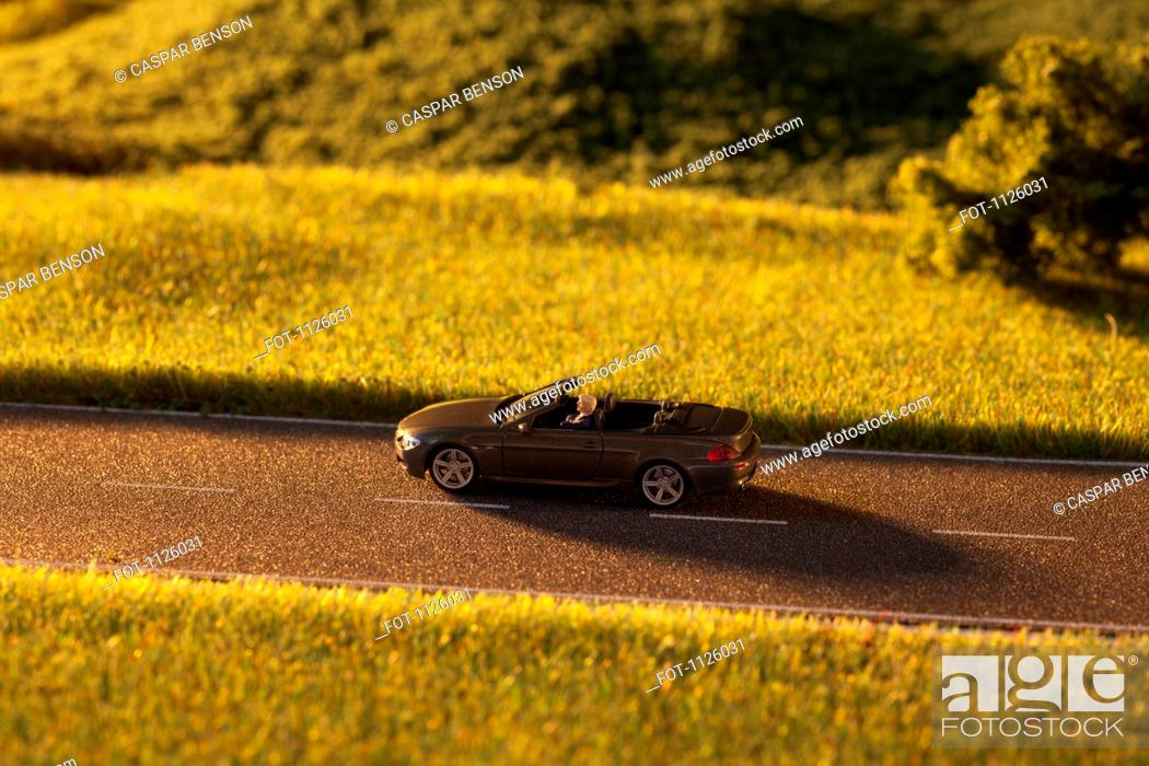 Photo de stock: A diorama of a miniature man driving a toy convertible sports car on a rural road.