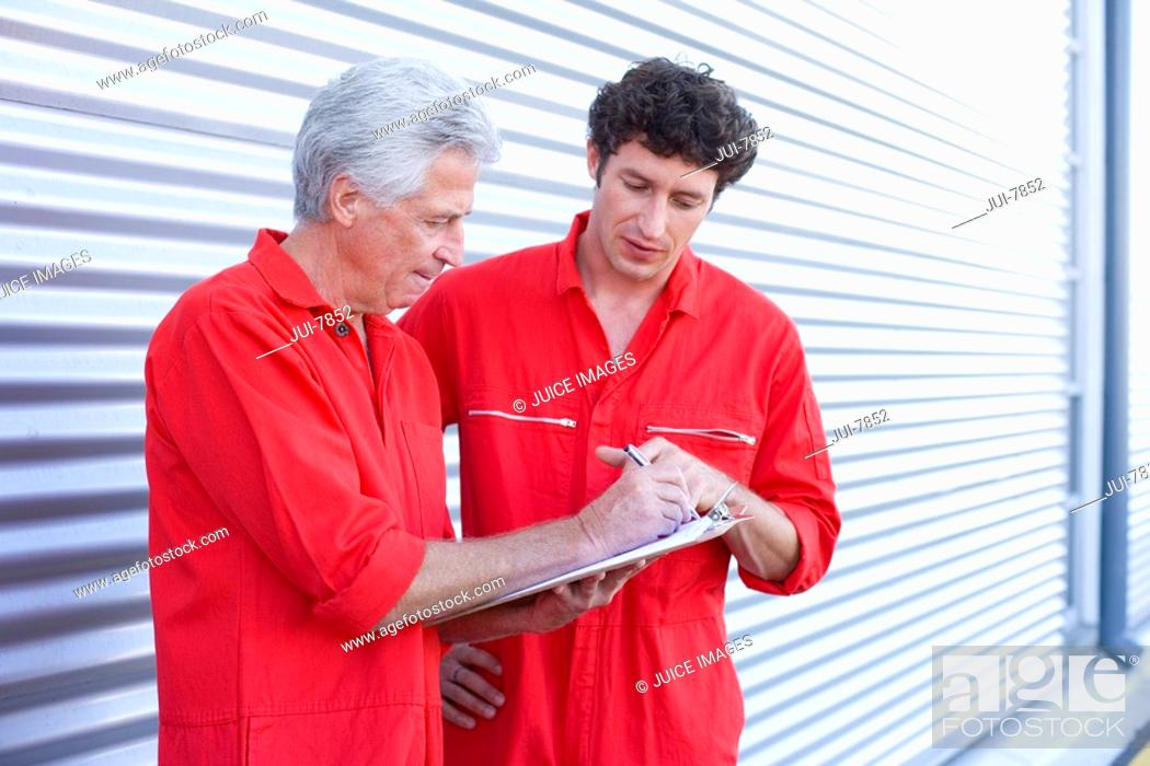 Stock Photo: Two car mechanics, in red overalls, standing outside closed rolling garage door with clipboard and pen, talking.