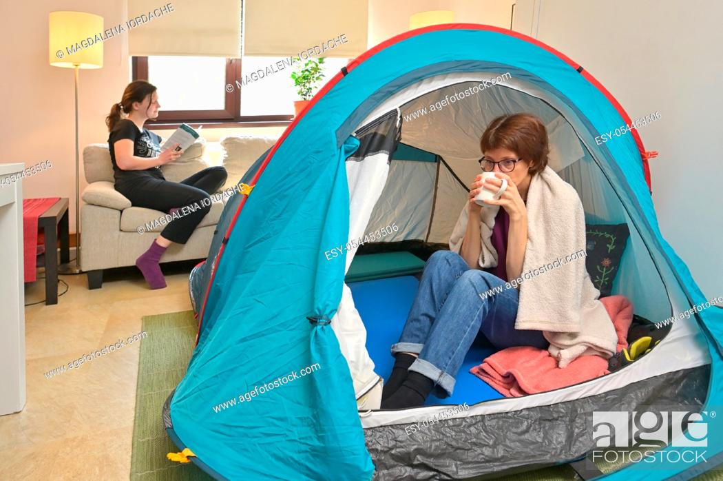 Stock Photo: Quarantine At Home. Mom And Daughter sit inside a tent enjoying a cup of tea.