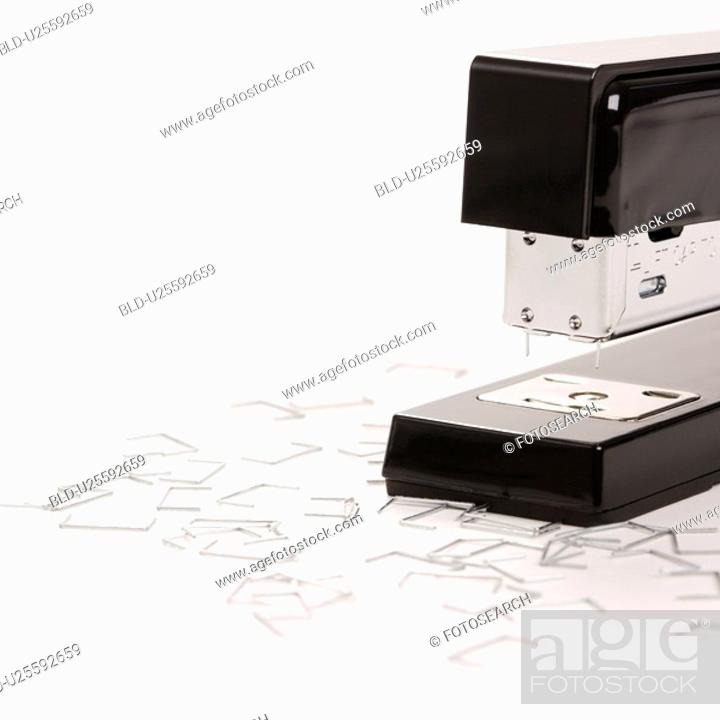 Stock Photo: Black stapler on white background surrounded by individual staples.