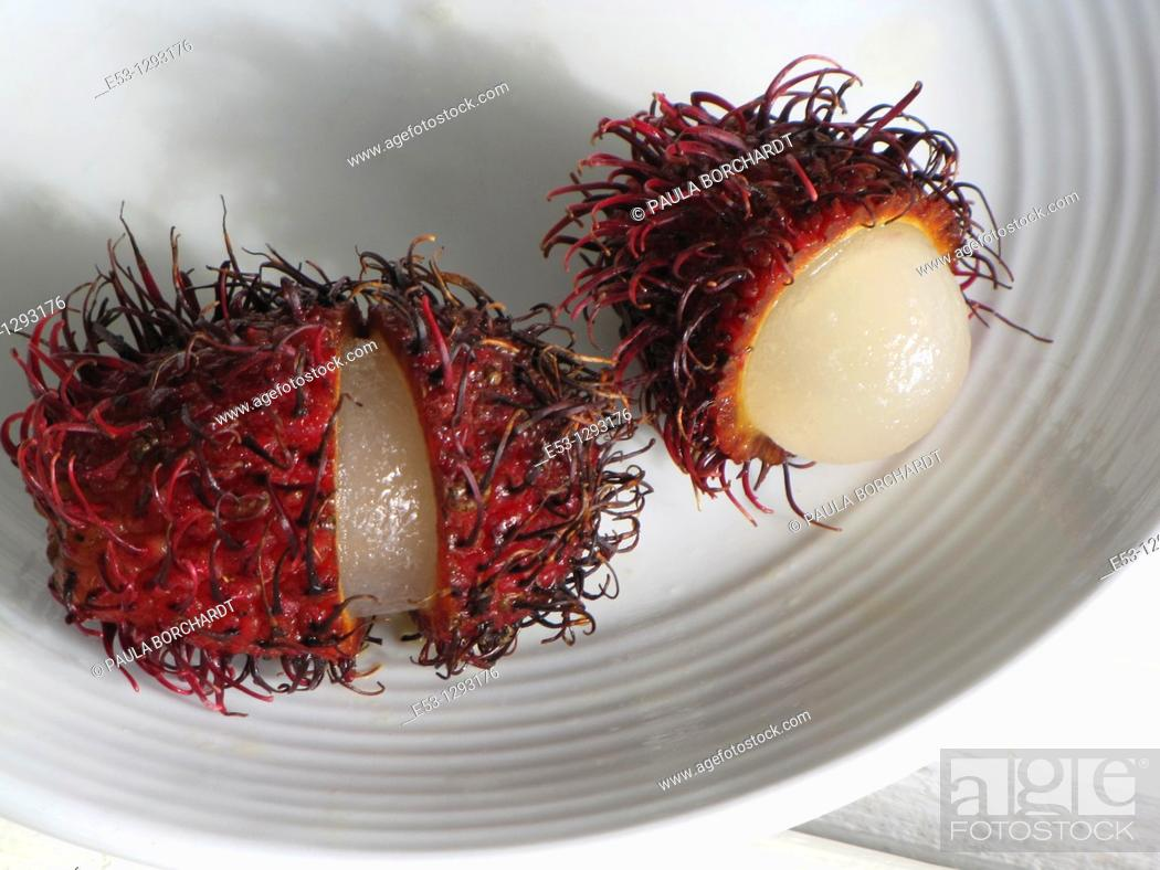 Stock Photo: Rambutan fruit cut open on plate, Big Island, Hawaii, USA.