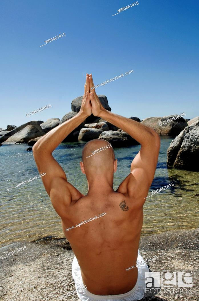 Imagen: Rear view of a young man practicing yoga.