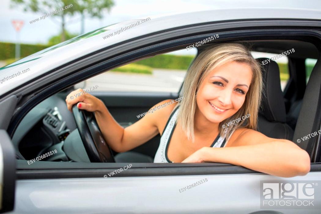 Imagen: Woman driving a car - female driver at a wheel of a modern car, looking happy, smiling with a relaxed smile (shallow DOF; color toned image).