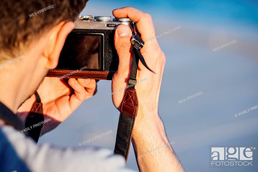 Stock Photo: Close-up of young man taking picture with old-fashioned camera.