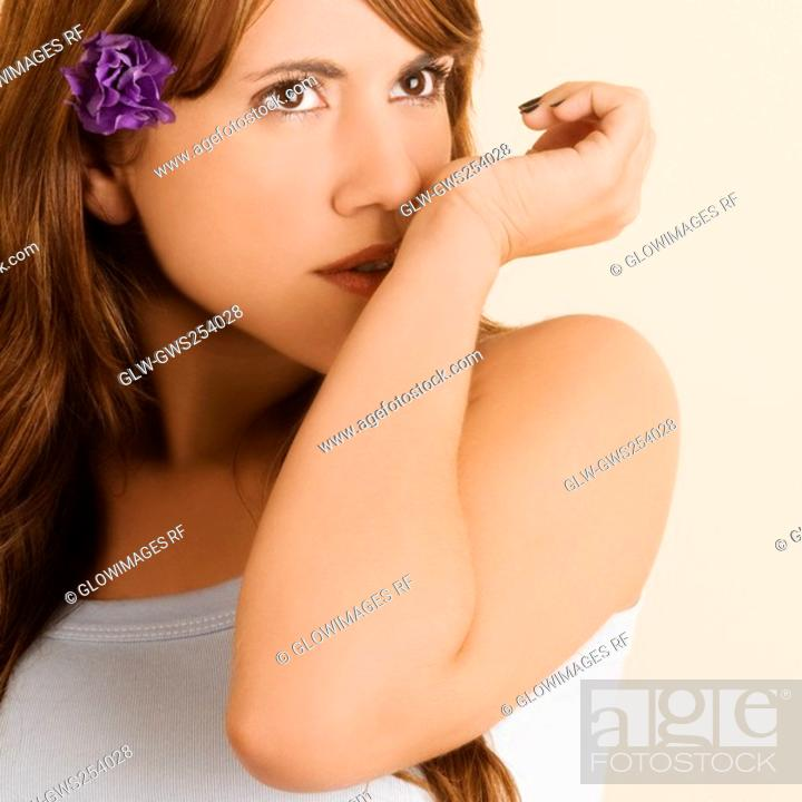 Stock Photo: Close-up of a young woman with a flower in her hair.