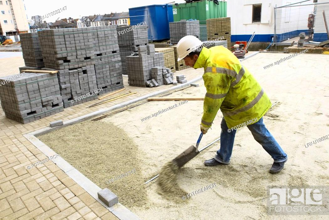 Stock Photo: Laying recycled glass material for paving stone. England, UK.