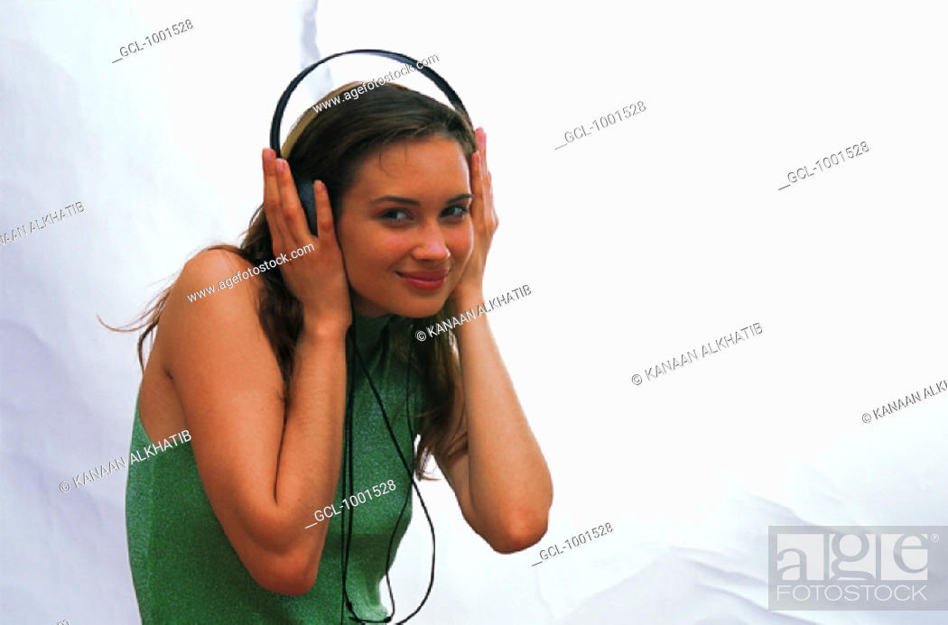 Stock Photo: Woman listening to music over headphones.