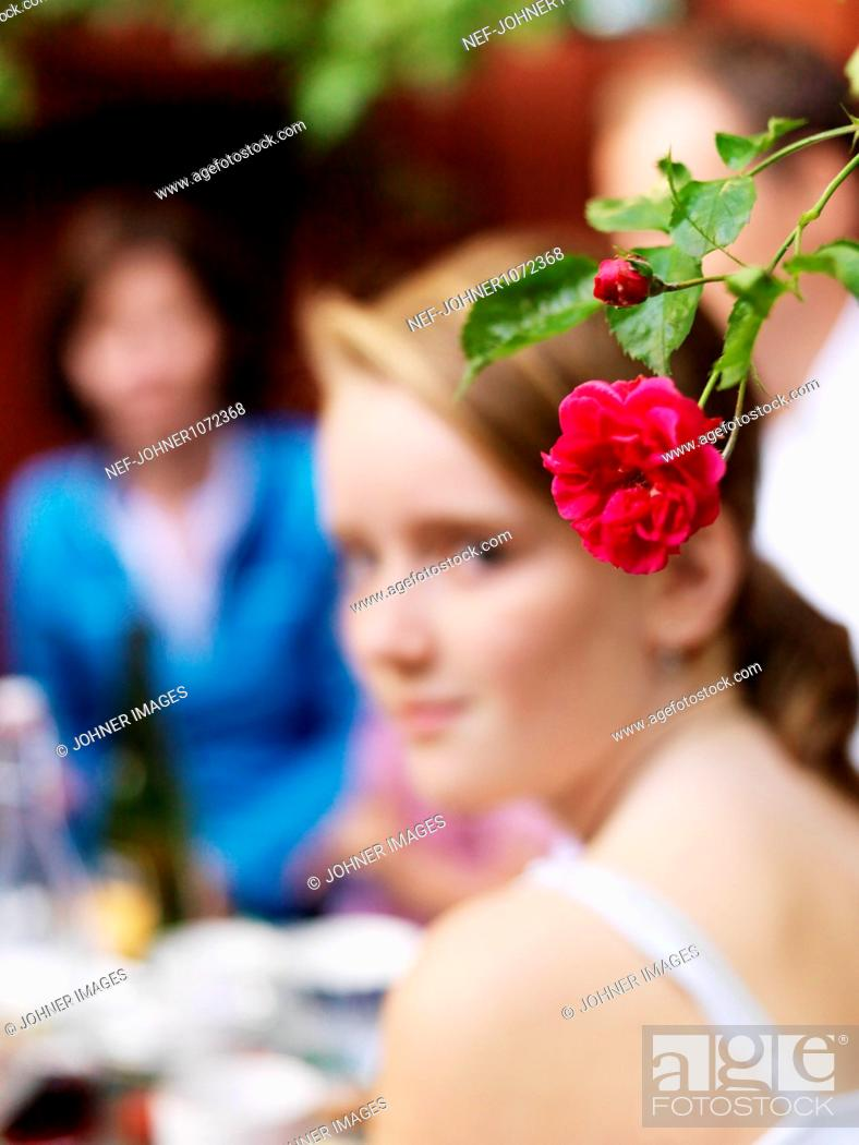 Stock Photo: Red rose and girl in background.