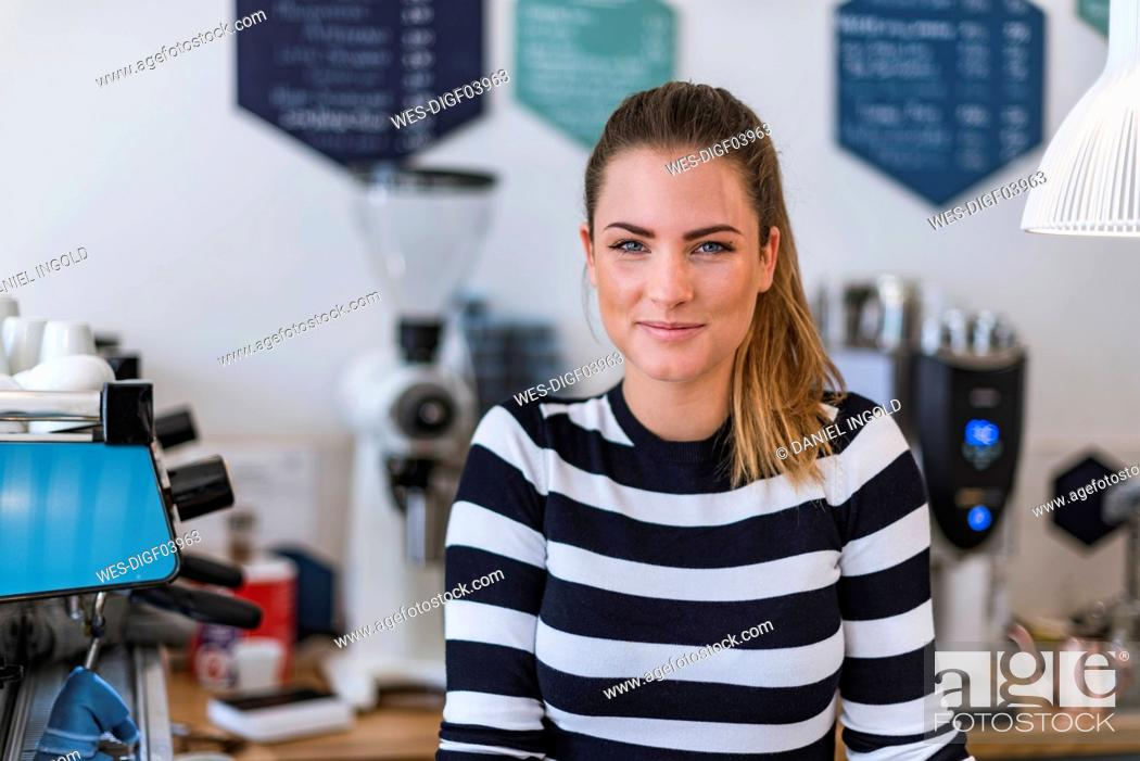 Stock Photo: Portrait of smiling young woman in a cafe.