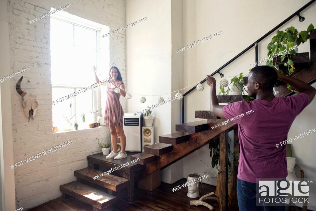Stock Photo: Young couple decorating loft with fairylights.