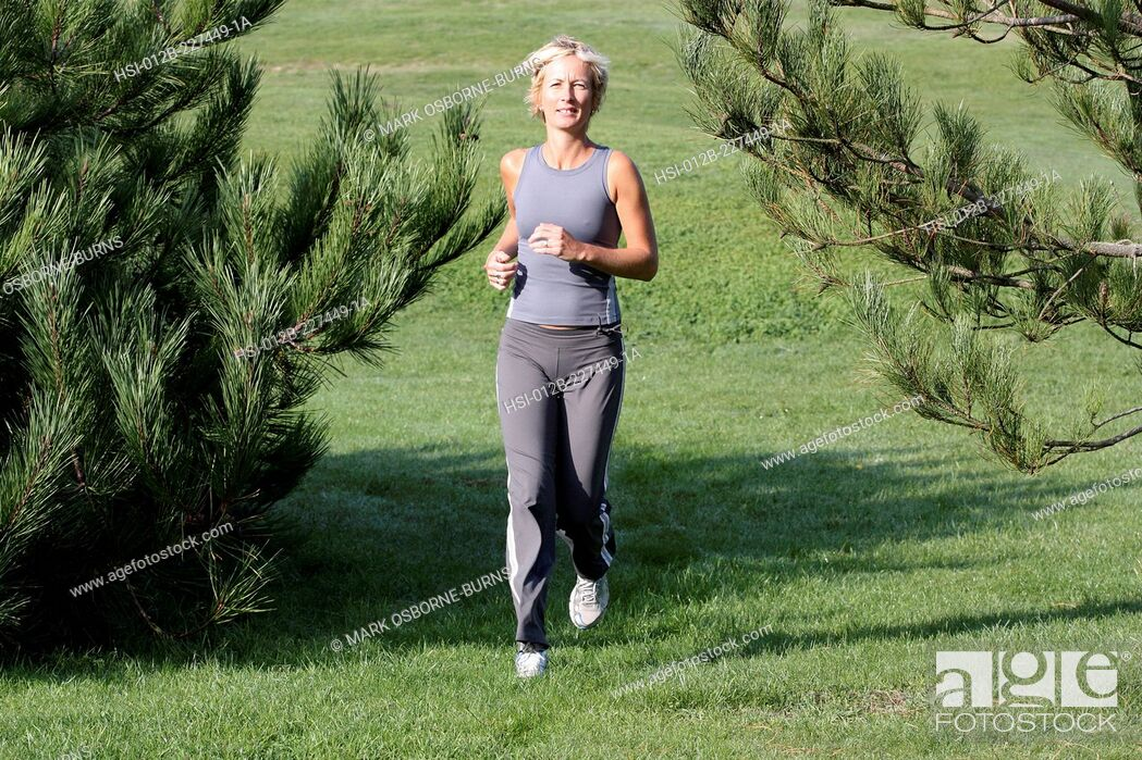 Stock Photo: Blonde woman outdoors. Jogging in countryside.