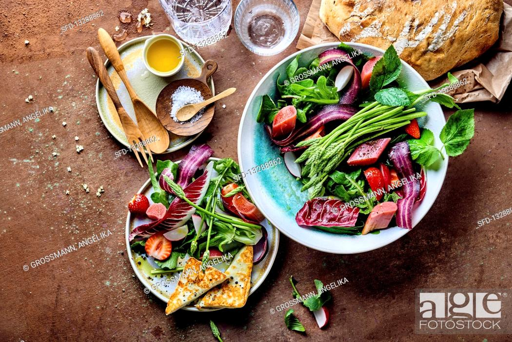 Stock Photo: Rhubarb salad with wild asparagus, strawberries, radicchio, oak leave lettuce and grilled cheese.