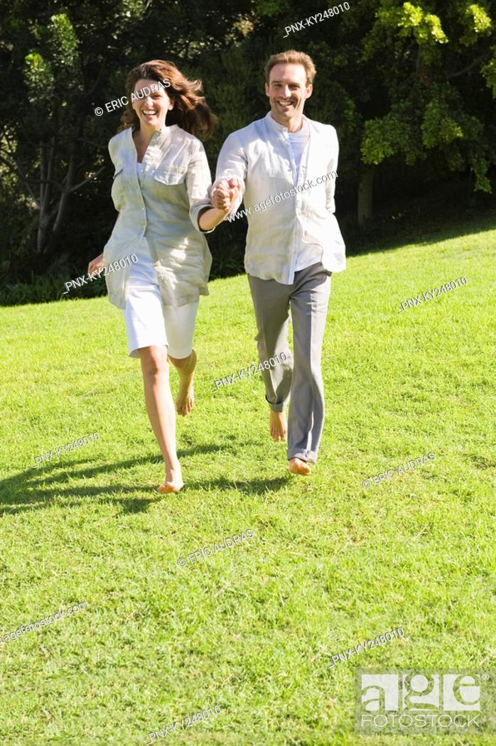 Stock Photo: Couple running on grass.