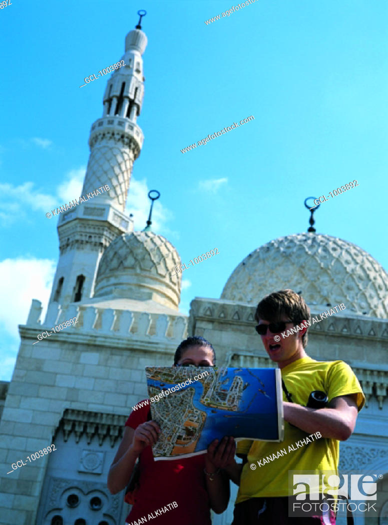 Stock Photo: Tourists looking at city map in front of Jumeirah Mosque in Dubai, United Arab Emirates.