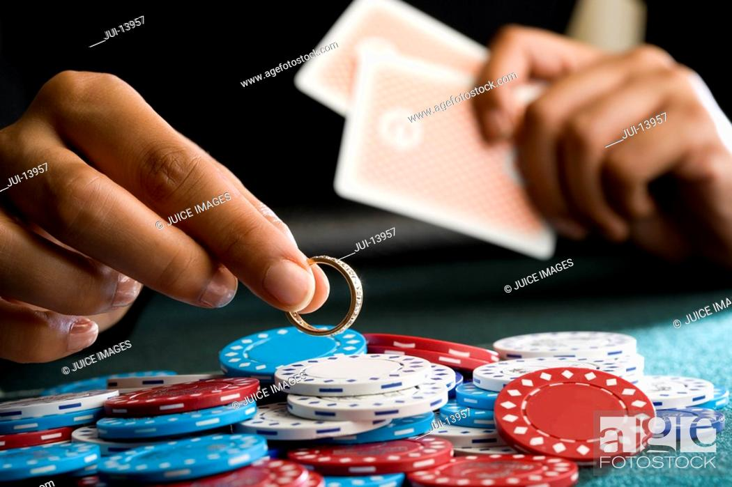 Stock Photo: Woman placing ring on pile of gambling chips on table, mid section.