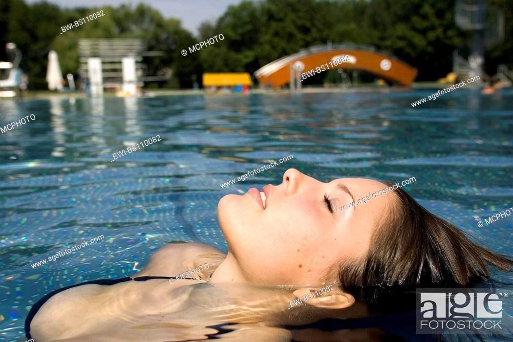 Stock Photo: young woman lying in water, Austria.