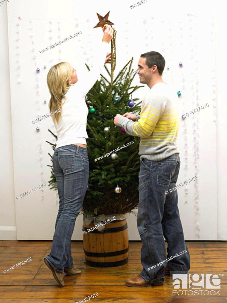 Stock Photo: Mid adult couple decorating christmas tree.