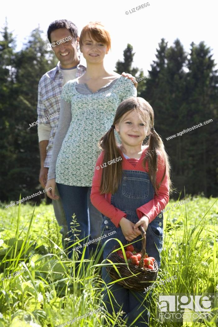 Stock Photo: Parents and daughter 5-6 in strawberry field portrait.