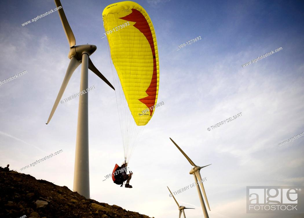 Stock Photo: A paraglider is taking off in between the wind turbines, what would be totally insane if these would be in service: It was while the installation of this.