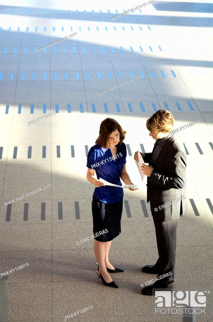 Stock Photo: High angle view of a businesswoman showing a document to a businessman.