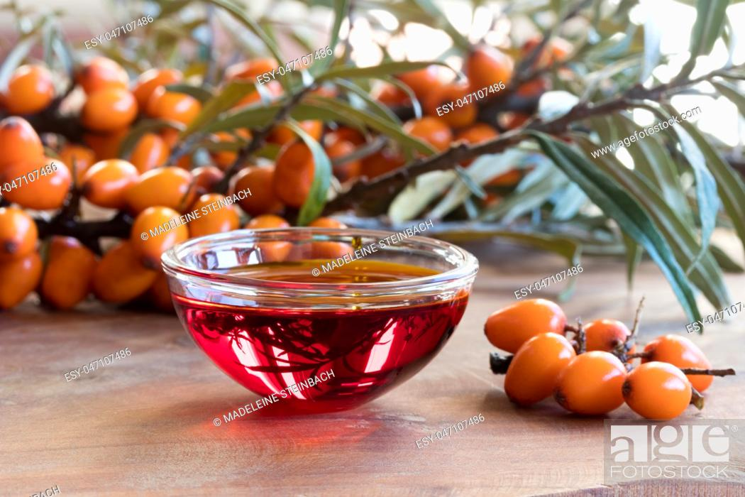 Imagen: Sea buckthorn oil in a glass bowl on a wooden table, with sea buckthorn berries and leaves in the background.