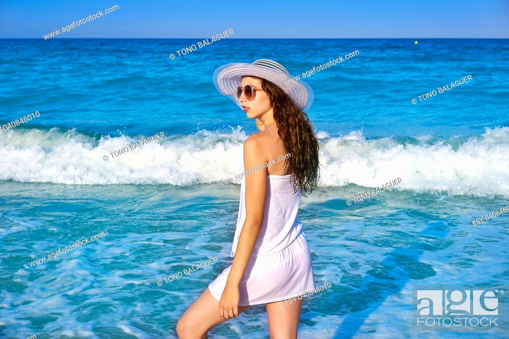 Stock Photo: Girl with beach hat in sea shore profile view with summer white dress.