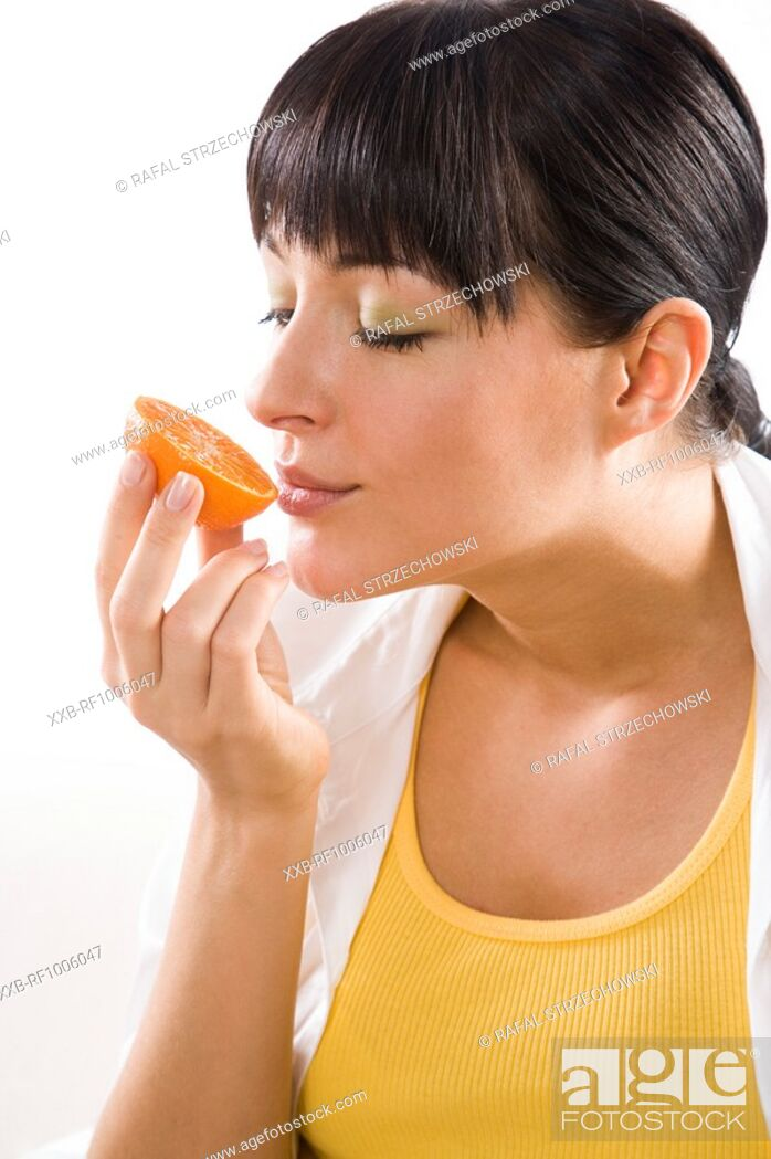 Imagen: woman holding half of mandarine.