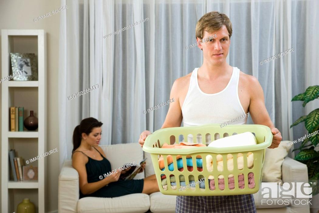 Stock Photo: A man doing laundry whilst a woman relaxes.