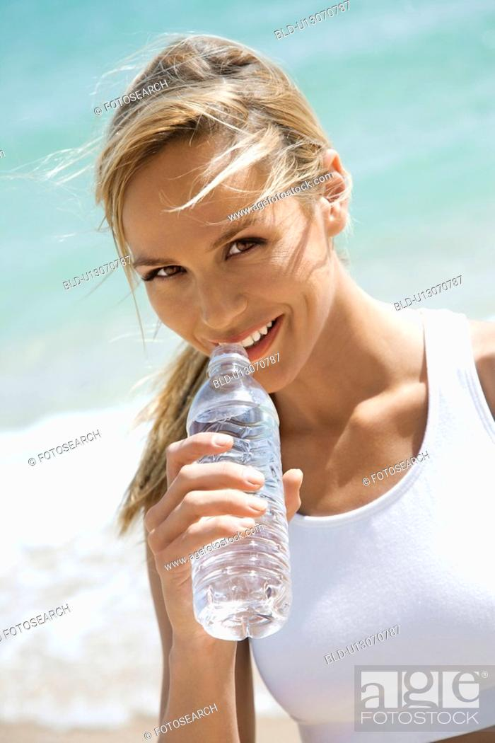 Stock Photo: Caucasian young adult woman drinking water on beach.